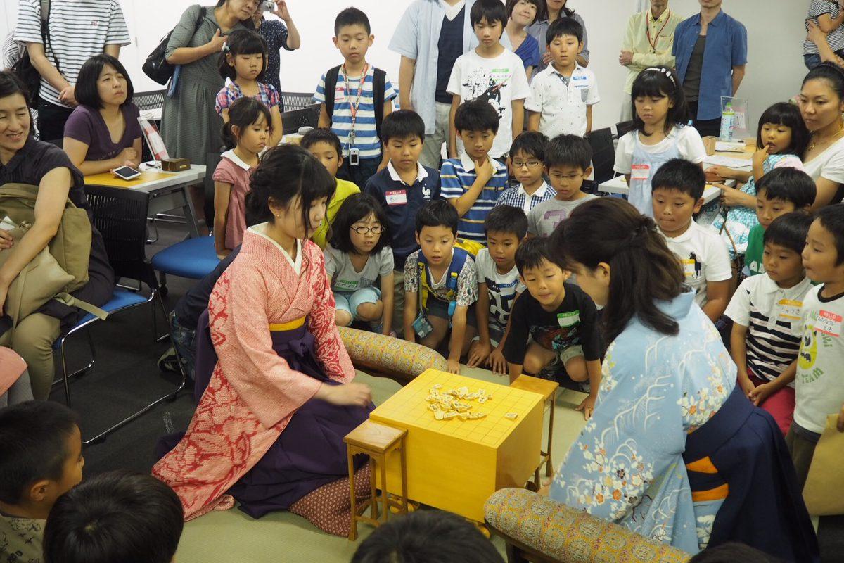 名人戦盤駒での対局デモンストレーションを見つめる子どもたち。