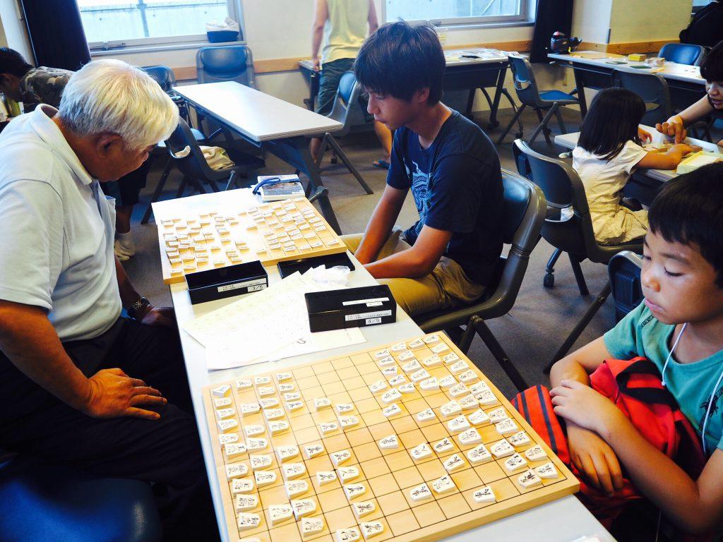 子どもたちと中将棋の二面指しをする武田会長。