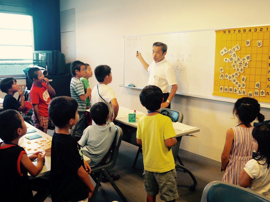 子どもたちに将棋の指導をする南里さん。