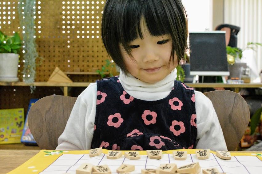 小さな子どもたちにとって、小さな駒をきちんと将棋盤のマス目に入れるのは難しい。