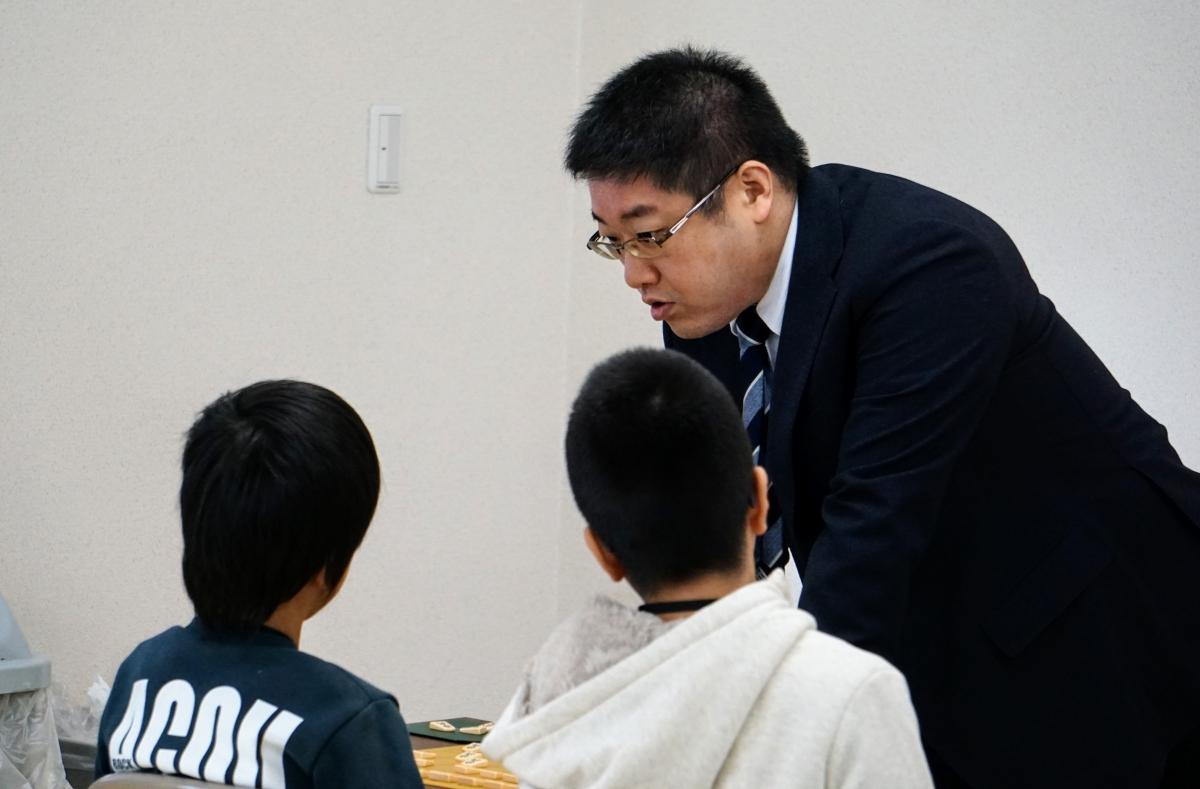 指導対局では、子どもたちになぜその手を指したのかについて考えてもらうと話す関口五段