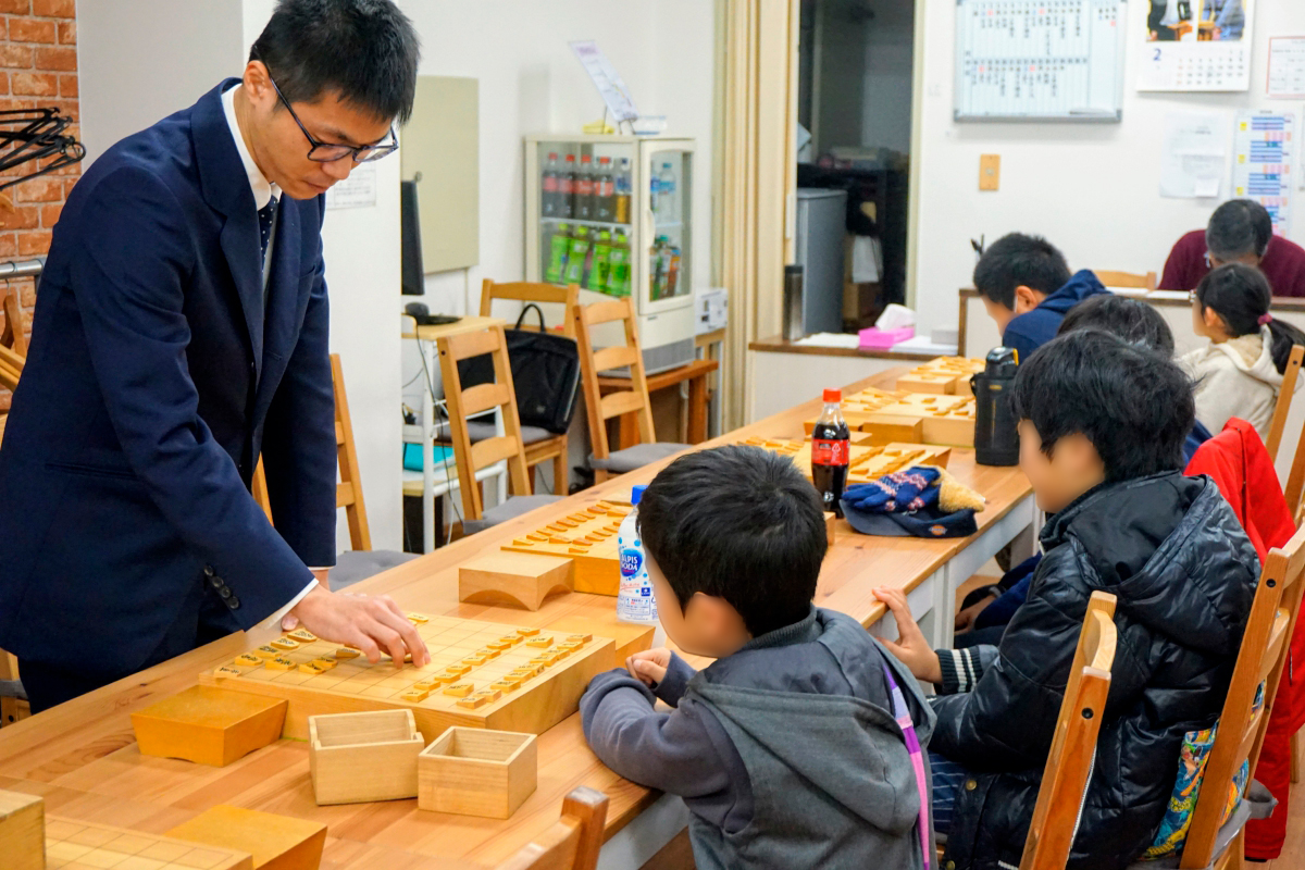 子どもたちに将棋の指導をする宮本五段