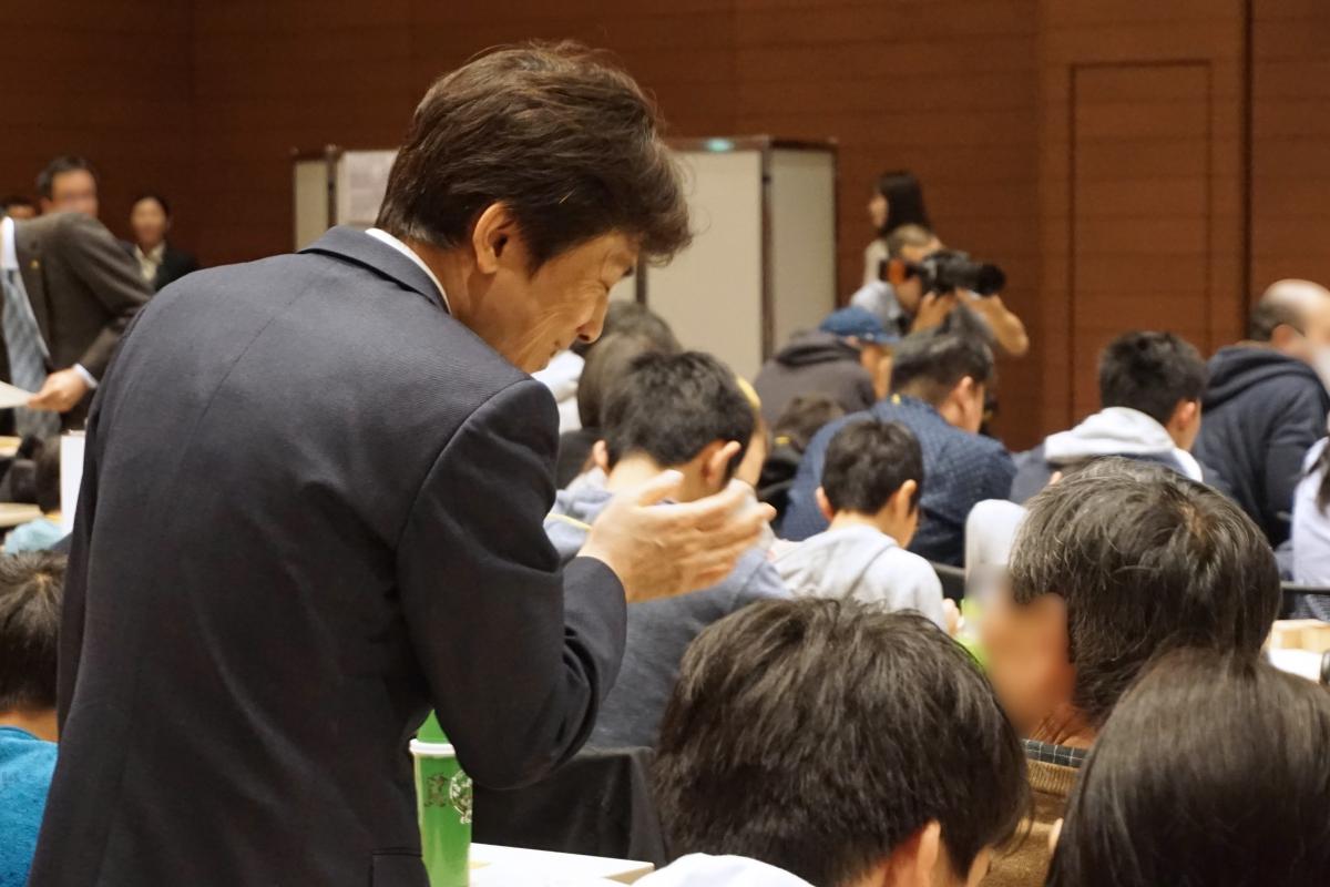 壇上から降りて詰将棋の指導をするプロ棋士の先生たち